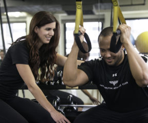 Trainer works with client on TRX exercises