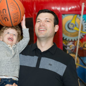 A dad and his son play with a basketball at Family Fun Night February 2017.