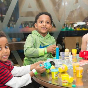 Three children play with Play-Doh at Family Fun Night February 2017.