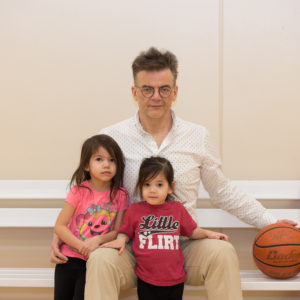 A father and two girls posing on a bench with a basketball.