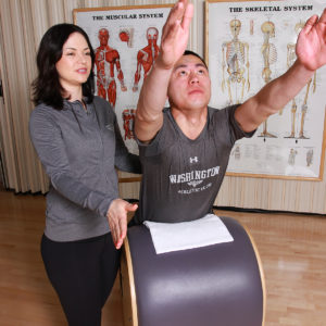Pilates instructor gives points to student.