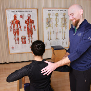 Pilates instructor adjusts back position with student