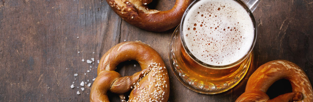 Glass of lager beer with traditional salted pretzels