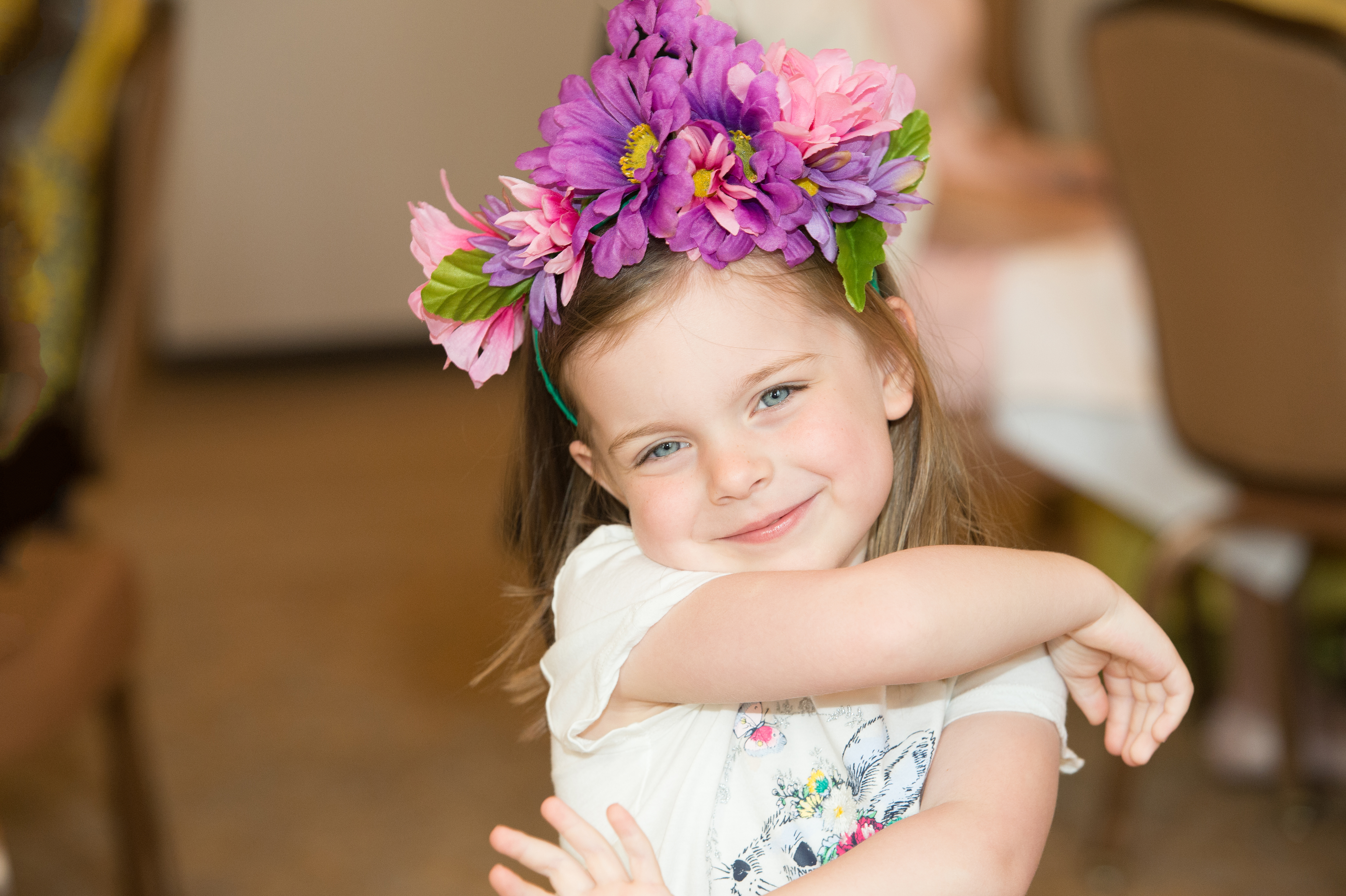fb6708203f A little girl wearing flower crown smiles for the camera.