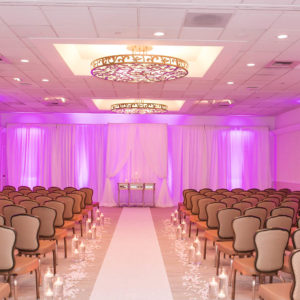 Image of room set up with rows of chairs and lit with colored lights and candles