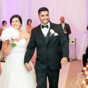 Man and woman dressed in wedding attire walking down an aisle looking happy
