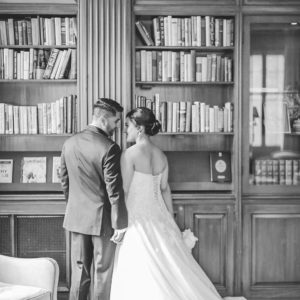 A man and woman dressed in wedding attire standing in front of bookshelves