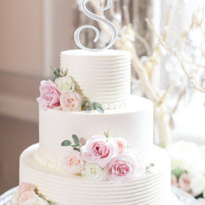 White wedding cake with a silver S on top and pink and white flowers