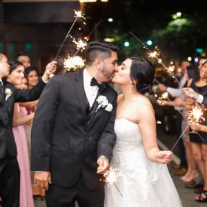 Man and woman in wedding attire holding sparklers in front of a crowd