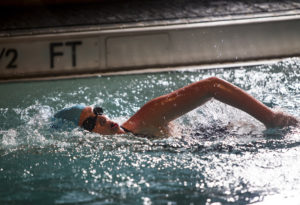 Swimmer moving through the water with freestyle stroke.