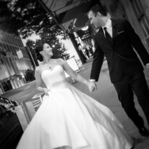 Couple in wedding attire holding hands and walking down a sidewalk