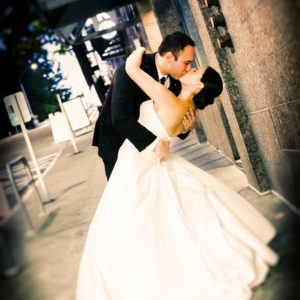 Couple in wedding attire kissing outside of the WAC