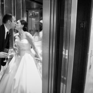 Couple in wedding attire kissing in an elevator
