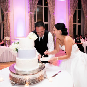 Couple cutting cake and laughing. They are dressed in wedding attire.