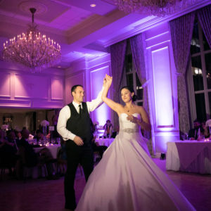 A couple in wedding attire dancing under chandeliers