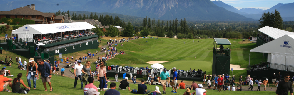 A crowd watches pro golfers with a vista of the Cascade Mountains.