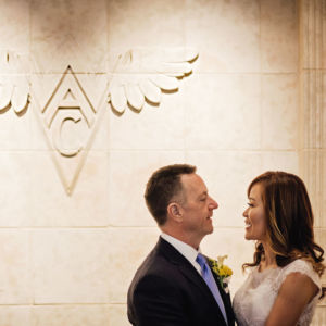 Couple standing in front of wall with WAC logo