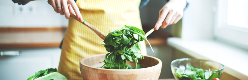 A woman in a yellow apron tosses mixed greens in a wooden bowl.