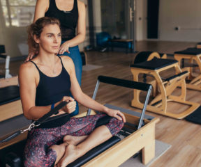 Fitness woman sitting with legs crossed on a pilates training machine and pulling the stretch band. Pilates trainer guiding a woman at the gym doing strength training.