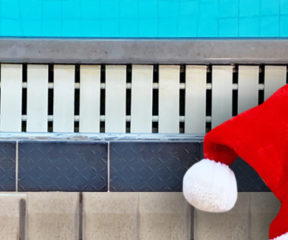 A Santa hat lies by the side of a pool.