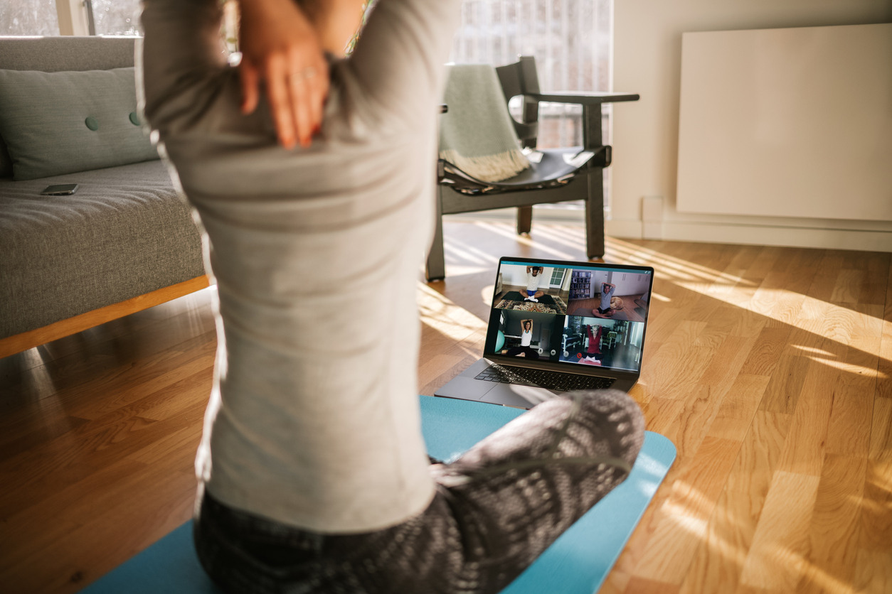 Yoga trainer demonstrating yoga poses to students via video conference.
