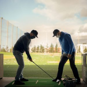 WAC golf instructor Gilbert Quitlong works with a male student on the driving range.