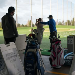 WAC golf instructor Gilbert Quitlong helps two students with their swings on the driving range.