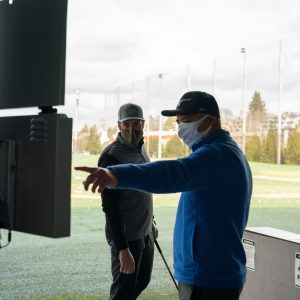 WAC golf instructor Gilbert Quitlong points to a screen to help a student analyze his stroke on the driving range.