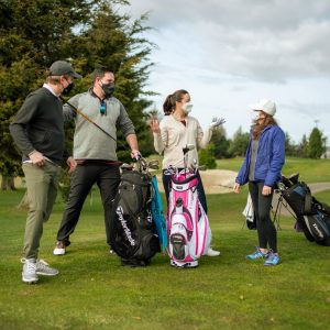 Two men and two women chat and laugh on the golf course.