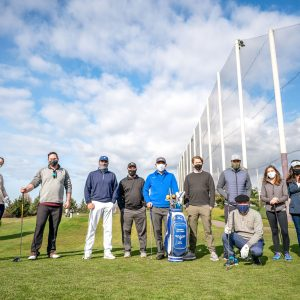 A group of WAC members wearing masks poses for the camera on the driving range.